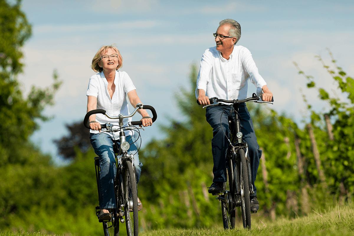 Older couple rides bikes outdoors