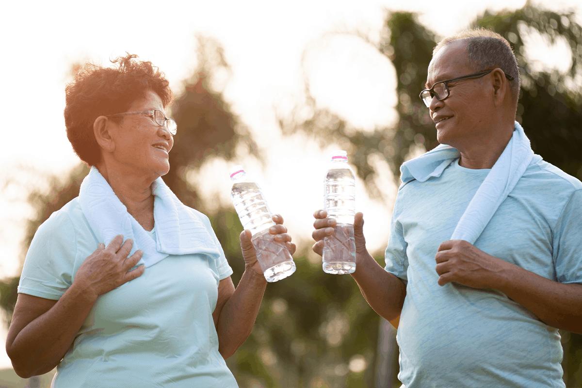 Older couple drink bottled water after exercise